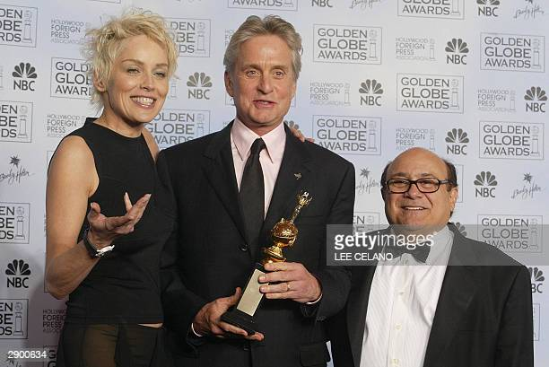 Actor Michael Douglas holds his Cecille B DeMille award with presenters Sharon Stone and Danny Devito at the 61st Golden Globe awards in Beverly...