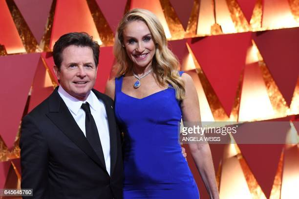 US actor Michael J Fox and his wife Tracy Pollan pose as they arrive on the red carpet for the 89th Oscars on February 26 2017 in Hollywood...