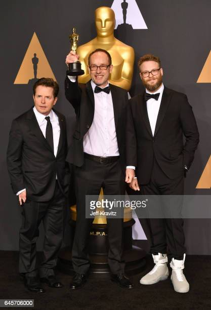 Actor Michael J Fox editor John Gilbert winner of Best Film Editing for 'Hacksaw Ridge' and actor Seth Rogen pose in the press room during the 89th...