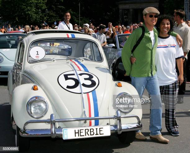 Actor Michael Keaton and director Angela Robinson pose beside a 'Herbie' designed car as thousands of Volkswagen Beetle drivers try to break the...