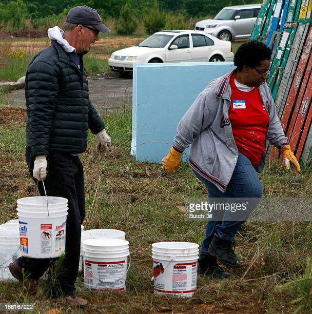 Actor Michael O'Neill caries a bucket for Tammie Griffin at a Habitat For Humanity home on May 6 2013 in Birmingham Alabama