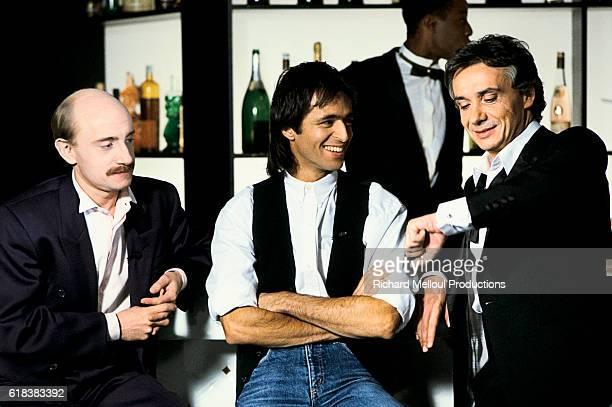 Actor Michel Blanc joins singers Jean-Jacques Goldman and Michel Sardou on the set of the television program Show Sardou.