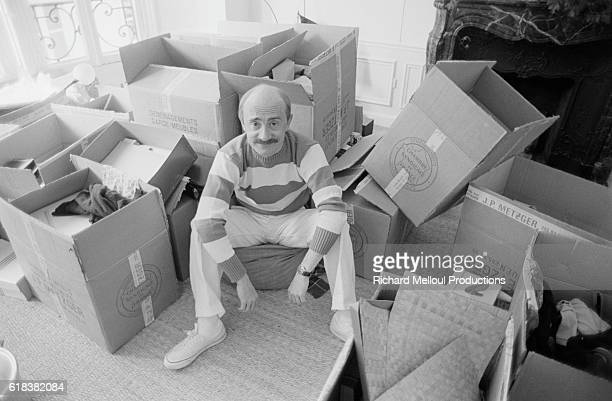Actor Michel Blanc moves into his new apartment. He sits in his living room surrounded by boxes.