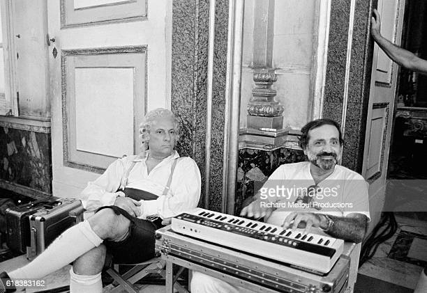 Actor Michel Serrault sits with French director Jean Yanne, who is playing a keyboard, on the set of the 1985 movie Liberte, Egalite, Choucroute ....