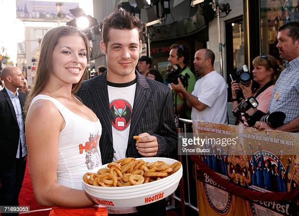 "Actor Mike Erwin poses with a Hooters girl as he arrives at the Warner Brothers premiere of ""Beerfest"" at the Grauman's Chinese Theatre on August 21,..."
