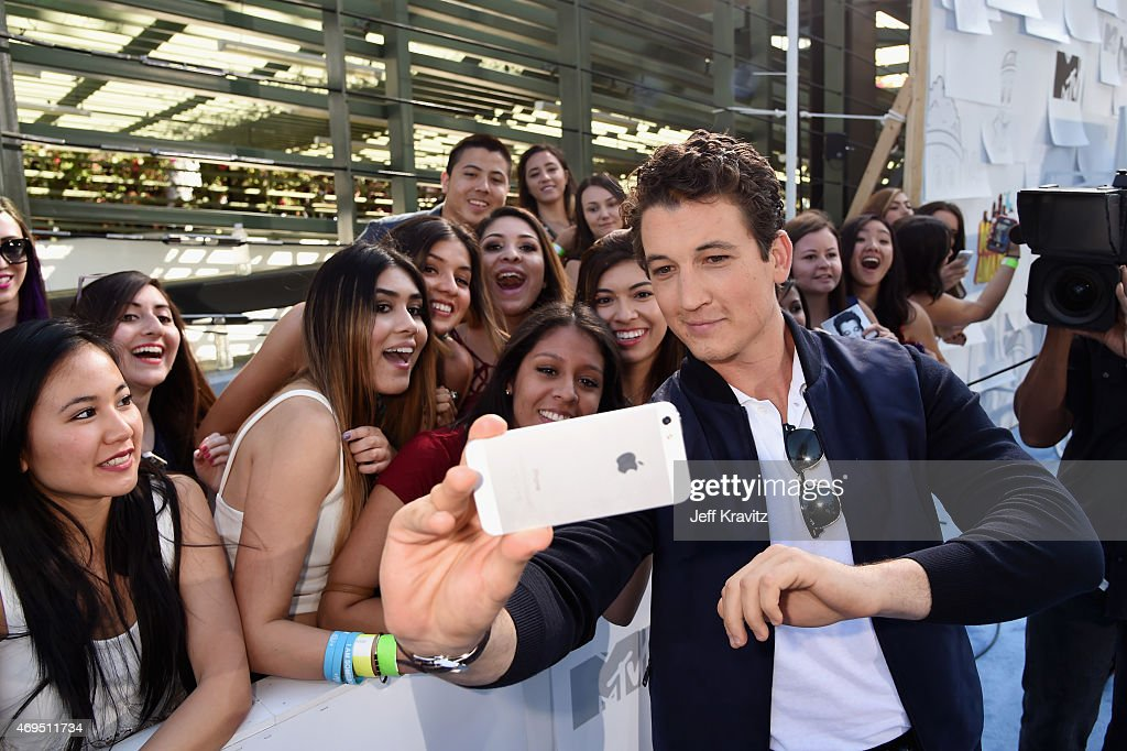 Actor Miles Teller takes a selfie with fans at The 2015 MTV Movie Awards at Nokia Theatre L.A. Live on April 12, 2015 in Los Angeles, California.