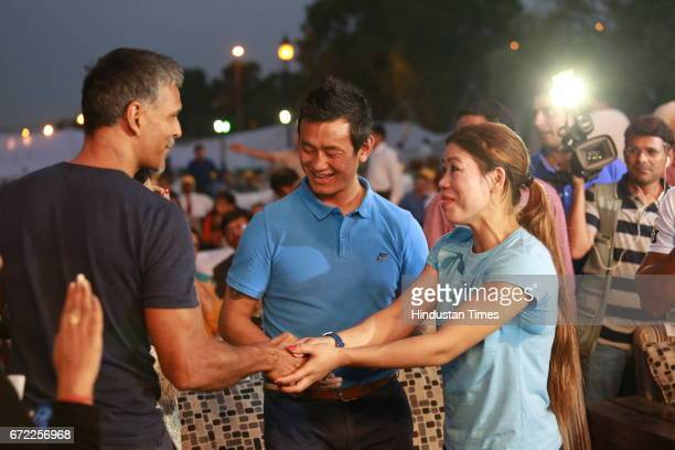 Actor Milind Soman greets Boxer Mary Kom and former India football skipper Bhaichung Bhutia during the launch of Oorja by CAFP U19 Football Talent...