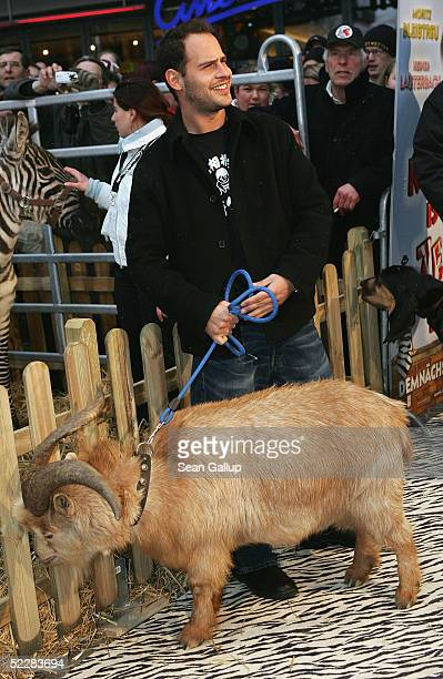 """Actor Moritz Bleibtreu clowns with a goat at the German premiere of """"Racing Stripes"""" on March 6, 2005 in Berlin, Germany."""