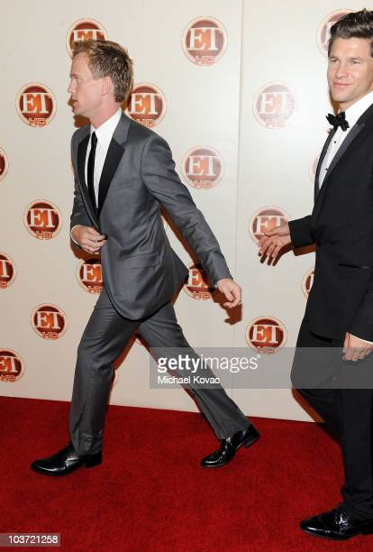 Actor Neil Patrick Harris runs down the red carpet as his partner David Burtka looks on at Entertainment Tonight's 62nd Annual EMMY After Party at...