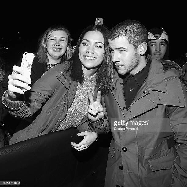 Actor Nick Jonas takes a selfie with a fan before the 'Goat' Premiere at Library Center Theater on January 22 2016 in Park City Utah