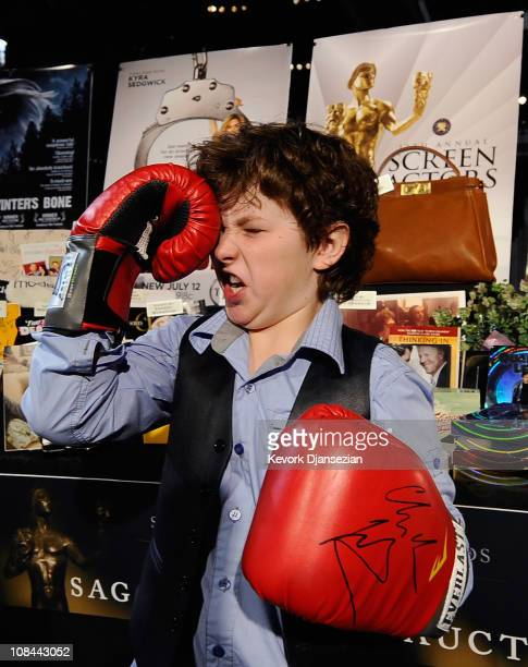 "Actor Nolan Gould nominated for his work in the television comedy series ""Modern Family"" poses with gloves autographed by actor Christian Bale and..."