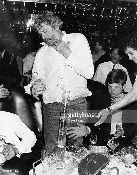 Actor Oliver Reed drunkenly balancing glasses on top of each other at his girlfriends 21st birthday party at Stringfellows London April 18th 1985