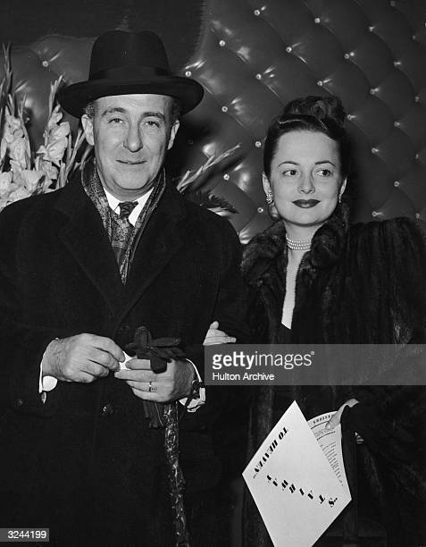 Actor Olivia de Havilland and her husband, Marcus Goodrich, standing together in front of a leather-cushioned wall at the premiere of directors...