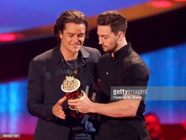 Actor Orlando Bloom accepts the Best Fight award for 'The Hobbit The Desolation of Smaug' from actor Aaron TaylorJohnson onstage at the 2014 MTV...