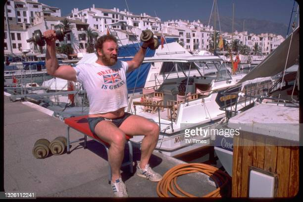 Actor Pat Roach in character as Brian 'Bomber Busbridge lifting weights on the Spanish set of comedy drama Auf Wiedersehen, Pet, circa 1986.