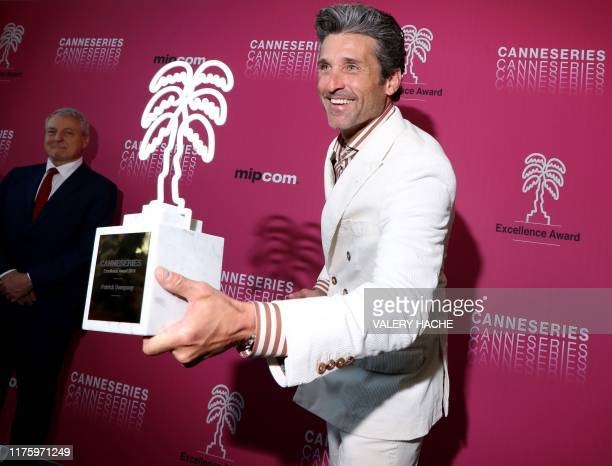 US actor Patrick Dempsey poses with 'Excellence Award' trophy for his career in the television and cinema at the MIPCOM the World's biggest...