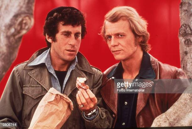 Actor Paul Michael Glaser holds a donut standing beside David Soul in a still from the television series 'Starsky and Hutch' circa 1977