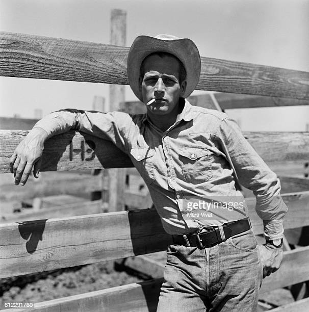 Actor Paul Newman leans against a fence smoking a cigarette on the set of the film Hud Near Claude Texas USA | Location near Claude Texas USA