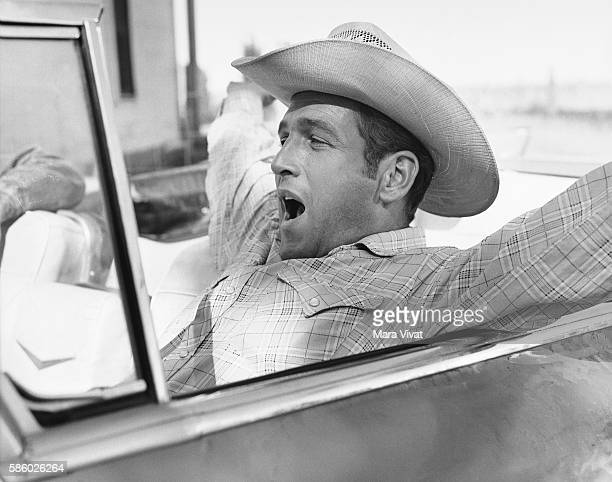 Actor Paul Newman yawns in a convertible car while shooting a scene for the film Hud Near Claude Texas USA | Location near Claude Texas USA