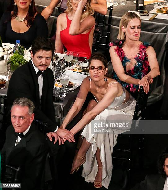 Actor Pedro Pascal and Amanda Peet share an embrace while actress Sarah Paulson looks on during The 22nd Annual Screen Actors Guild Awards held at...