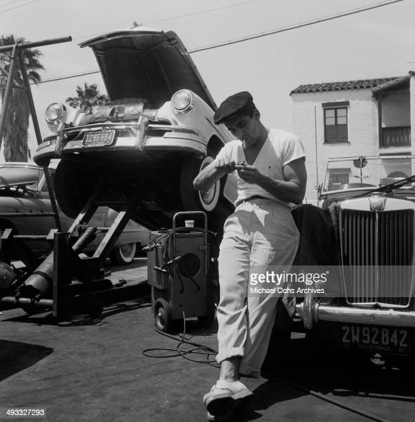 Actor Perry Lopez poses on a car in Los Angeles California