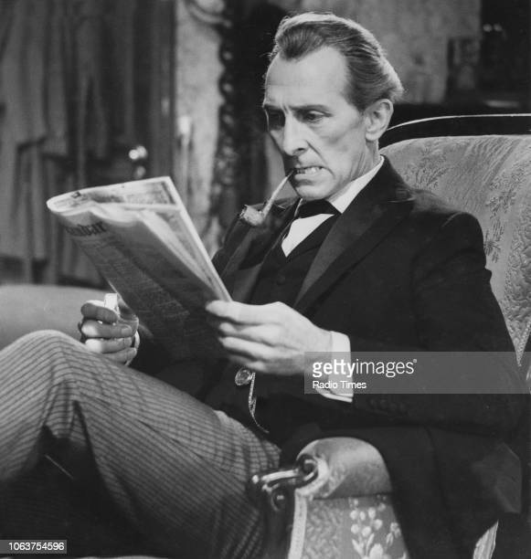 Actor Peter Cushing smoking a pipe and reading a newspaper in a scene from the episode 'A Study in Scarlet' of the television show 'Sherlock Holmes'...