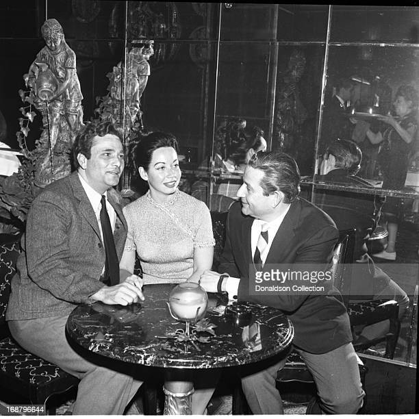 Actor Peter Falk poses for a portrait with his wife Alyce Mayo and a man at Cheers Restaurant on West 41st Street on March 15 1965 in New York New...
