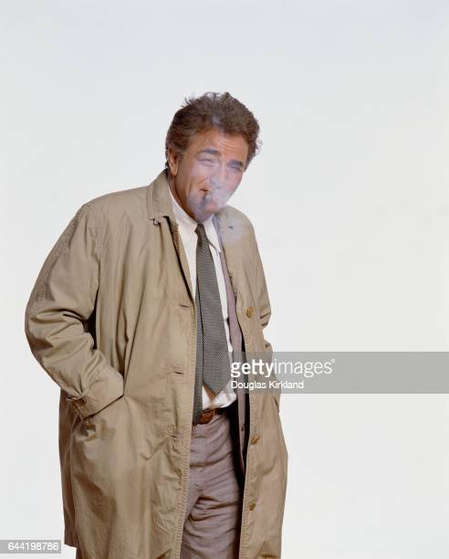 Actor Peter Falk smokes a cigar and wears the trademark rumpled rain coat of his character Lieutenant Columbo from the Columbo television movies
