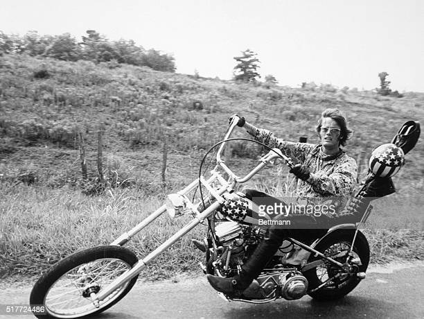 """Actor Peter Fonda rides a cool sleek motorcycle - known to motorcycle enthusiasts as a """"chopper"""" bike with a """"raked"""" front--in a scene from his..."""