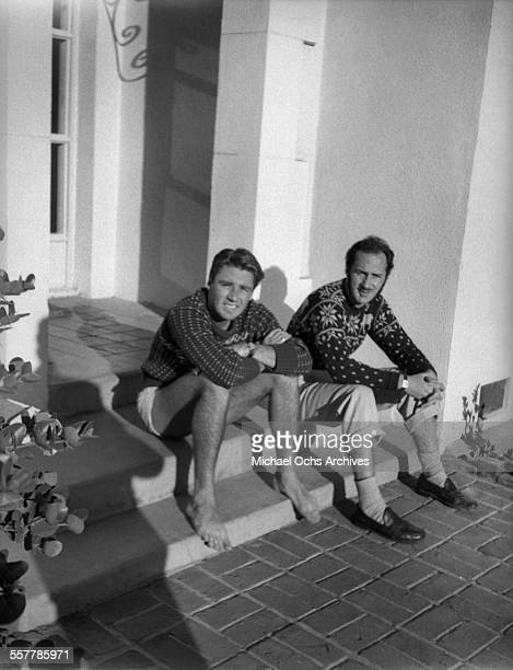 Actor Peter Lawford and actor Keenan Wynn pose on the steps of a house in Los Angeles California