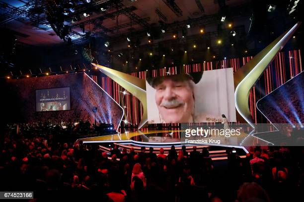 Actor Peter Simonischek on the screen after he wins Best Actor awarded to him by Alexandra Maria Lara on stage at the Lola German Film Award show at...