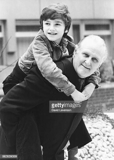 Actor Peter Vaughan carrying young child actor Richard Wainbaum on his back who is playing his grandson during filming for the television series...
