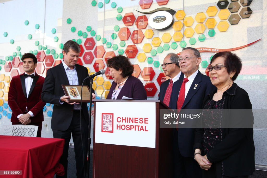 Actor Philip Ng (L) and director George Nolfi (center L) present Chinese Hospital CEO Brenda Yee (C) with a commemorative plaque at a special press conference of BH Tilt & WWE Studios' 'Birth of the Dragon' at the San Francisco Chinese Hospital on August 16, 2017 in San Francisco, California.