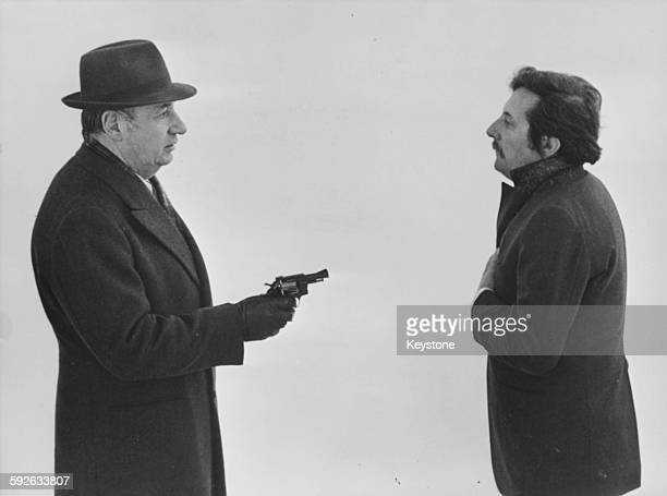 Actor Philippe Noiret points a gun at Jean Rochefort in a scene from the film 'Birgit Haas Must Be Killed' 1981