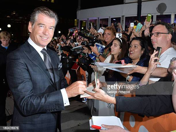 Actor Pierce Brosnan signs autographs as he arrives at the 'Love Punch' Premiere during the 2013 Toronto International Film Festival at Roy Thomson...