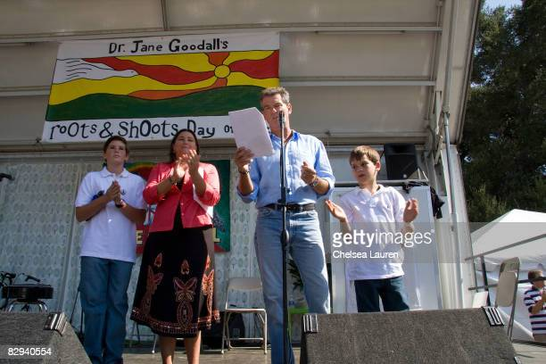 Actor Pierce Brosnan speaks while his wife Keeley Shaye Smith and their sons Dylan and Paris applaud on stage during Roots Shoots Day of Peace at...