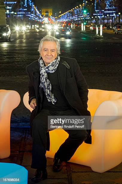 Actor Pierre Arditi sits on a television set on place de la Concorde with the Christmas decorations of the Champs Elysees avenue behind during the...