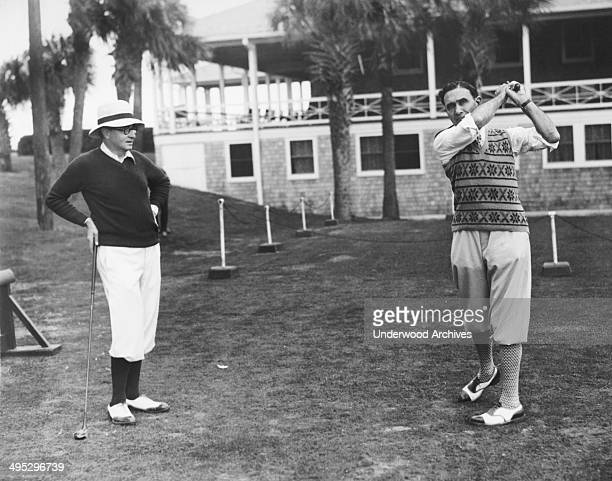 Actor playwright director and producer Edgar Selwyn tees off as mystery writer Arthur Somers Roche looks on at the annual Artists and Writers Golf...