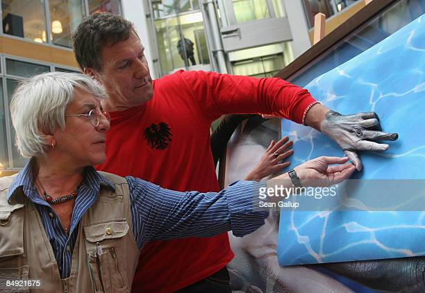 Actor Ralf Moeller poses with his hand painted like the head of a dolphin as Italian artist Guido Daniele adjusts a finger at the opening Guido...