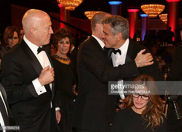 Actor Ralph Fiennes hugs filmmaker George Clooney and actress Julia Roberts as they attend the 2013 BAFTA LA Jaguar Britannia Awards presented by BBC...