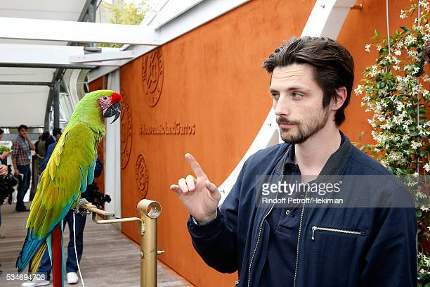 Actor Raphael Personnaz and parrot Zoe attend the 2016 French Tennis Open Day Six at Roland Garros on May 27 2016 in Paris France