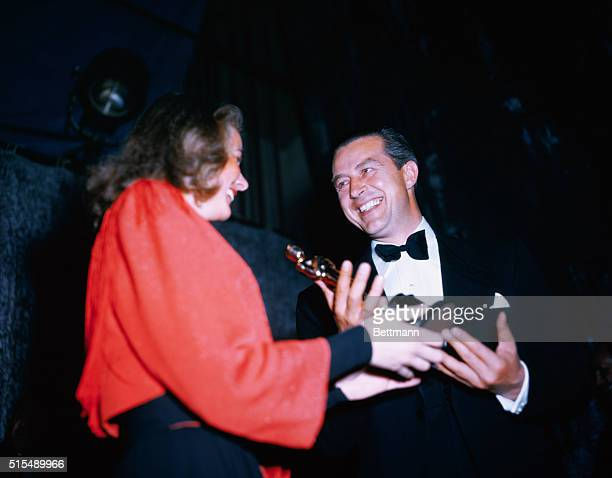 Actor Ray Milland happily accepts his Oscar statuette for The Lost Weekend from one of the previous year's winners Ingrid Bergman