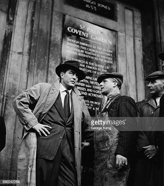 Actor Ray Milland talking to market porters, waiting for filming to begin in Covent Garden, London, circa 1945.