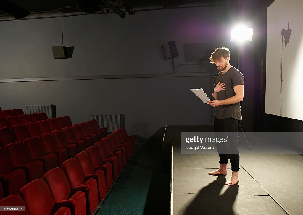 Actor rehearsing his lines on stage. : Stockfoto