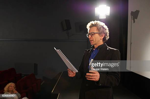 Actor rehearsing on stage under spotlight.