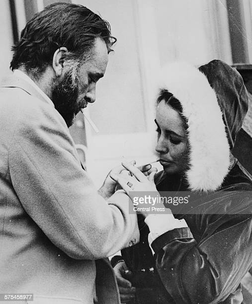 Actor Richard Burton lighting a cigarette for his wife Elizabeth Taylor outside their chalet in Gstaad March 7th 1966