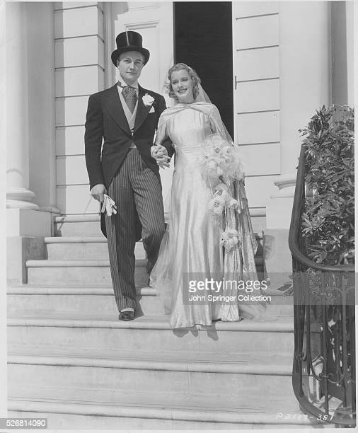 Actor Richard Denning and actress Ellen Drew model fashionable 1930's wedding attire as as they pose as bride and groom
