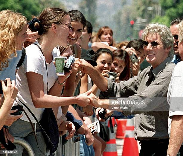 US actor Richard Gere shakes hands with fans after he placing his hands and feet in cement during ceremony at Mann's Chinese Theatre 26 July 1999 in...