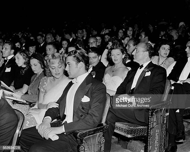 Actor Richard Greene and Anita Louise and actress Myrna Loy sits behind them at a premiere in Los Angeles California
