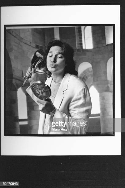 Actor Richard White admiring himself in hand mirror as he holds two others in front of backdrop at studio acting like the character Gaston for whom...